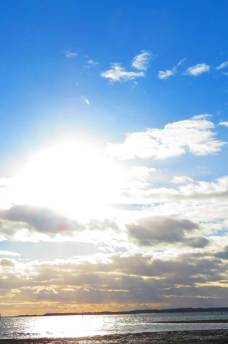 Besprechen von Krankheiten - Sonne scheint am Mittagshimmel hinter Wolken