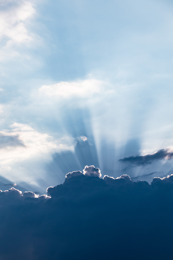 Besprechen von Krankheiten - Sonnenstrahlen hinter Wolken hervorbrechend