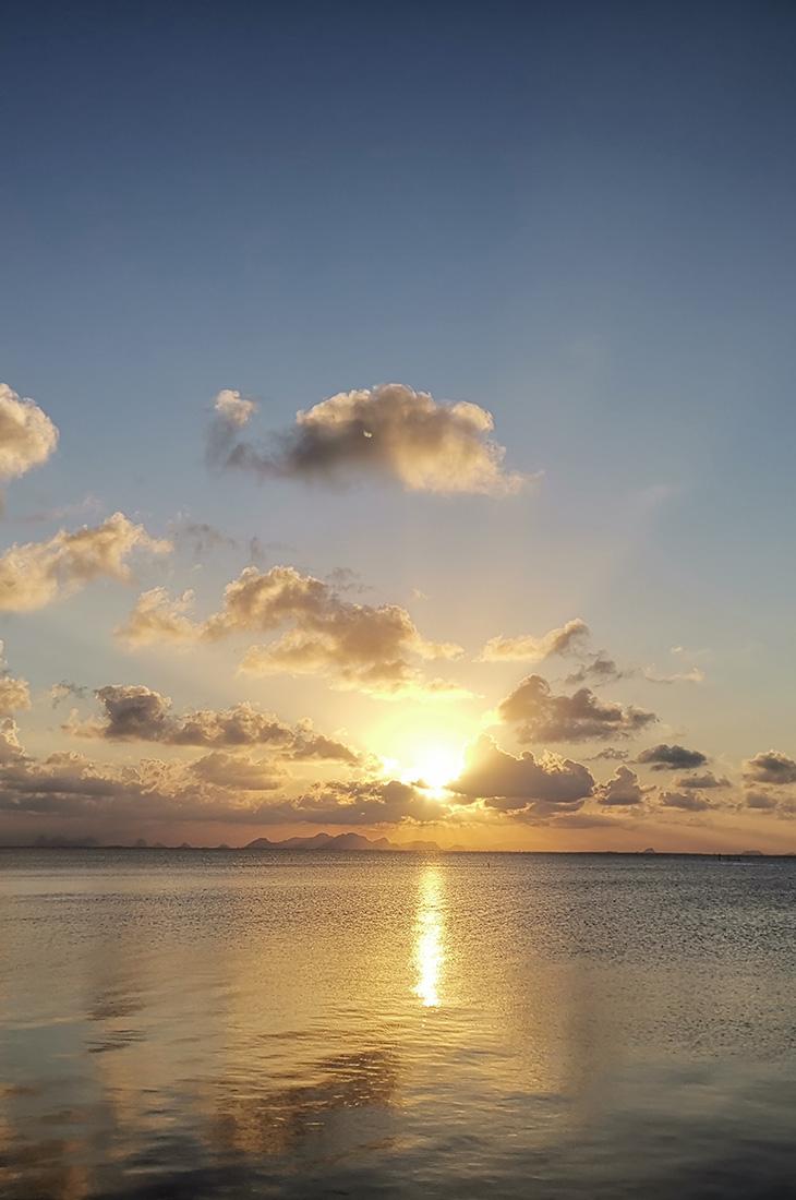 Besprechen von Krankheiten - Sonnenstrahlen hinter Wolken über dem Meer