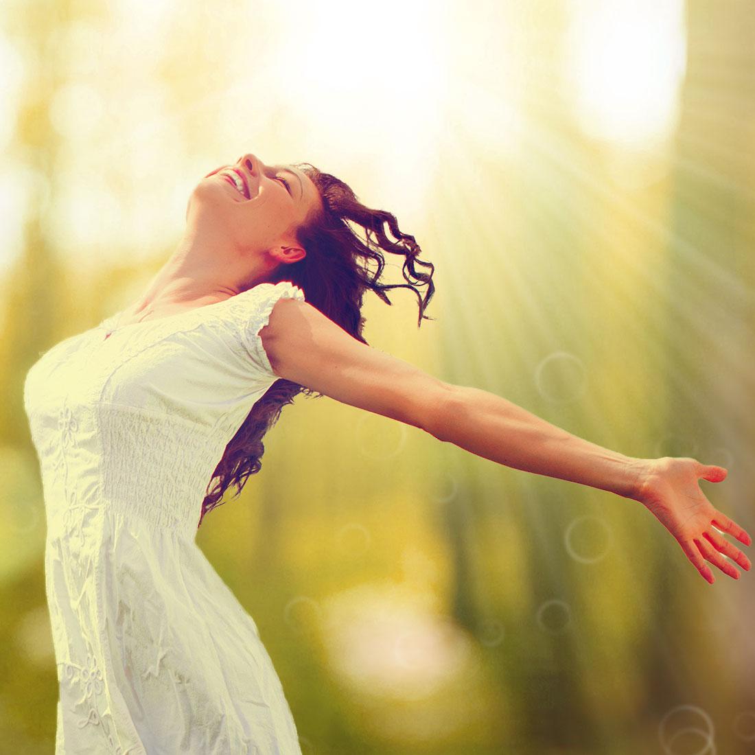 Besprechen von Krankheiten - gesunde glückliche Frau tanzt im Wald im Licht