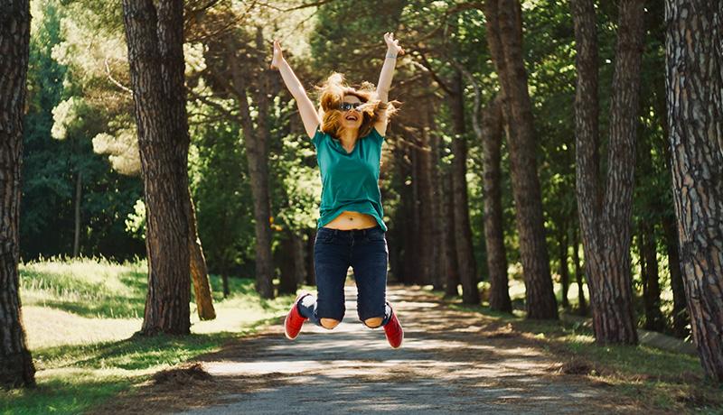 Krankheiten besprechen - Frau springt im Wald in die Luft