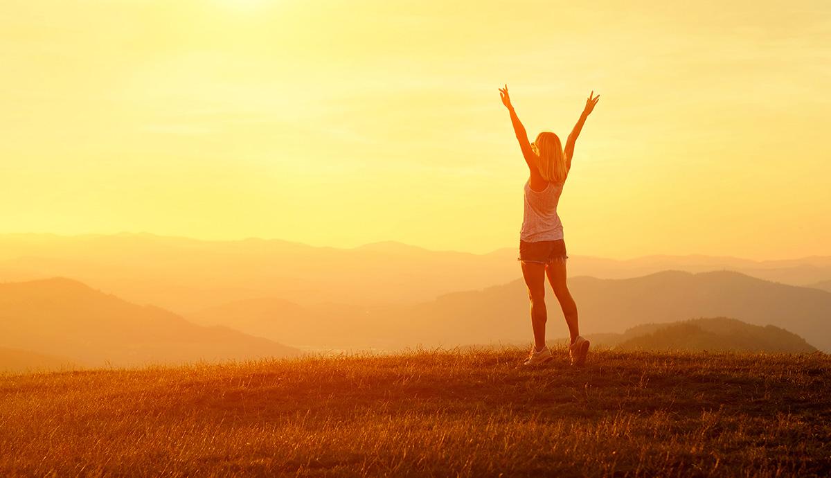 Besprechen von Krankheiten - Glückliche Frau vor Sonnenaufgang in Landschaft